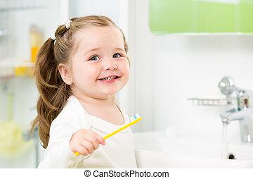 Smiling child girl brushing teeth in bathroom