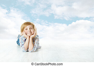 Smiling child lying down, small kid looking at camera. Blue sky and clouds