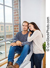 Smiling couple relaxing on a windowsill