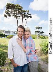 Smiling couple standing outside together in their garden