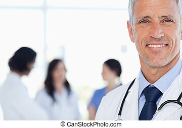 Doctor showing a beaming smile with his medical interns behind him