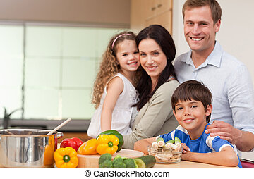 Smiling family standing in the kitchen