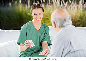 Smiling Female Nurse Playing Cards With Senior Man