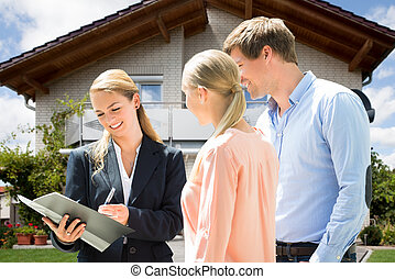 Real Estate Agent Explaining Contract To Couple Buying House