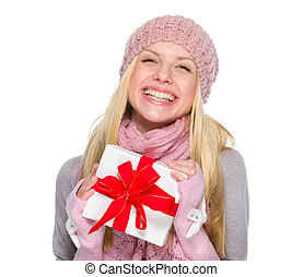 Smiling girl in winter clothes holding present box