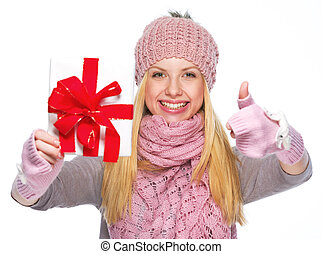 Smiling girl in winter clothes showing christmas presenting box and showing thumbs up