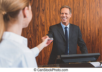 Smiling hotel manager welcoming woman