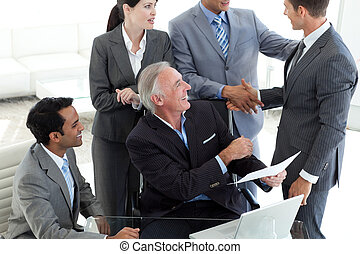 Smiling international business people studying a document in a meeting
