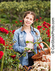 female posing near roses and holding a basket in the garden