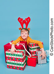 Smiling kid holding a pile of gift boxes on blue background