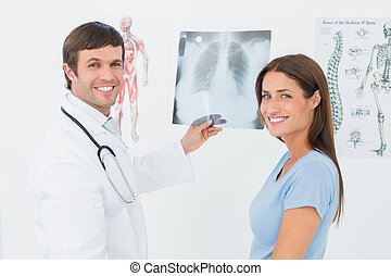 Smiling male doctor explaining lungs x-ray to female patient