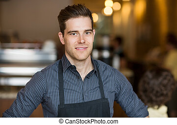 Smiling Male Owner In Cafe