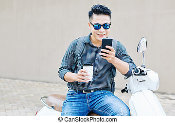 Smiling man checking notifications on smartphone