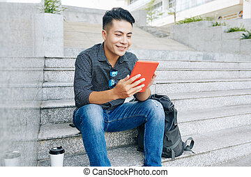 Smiling man reading article online
