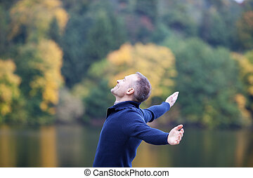 Smiling Man With Arms Outstretched Against Lake