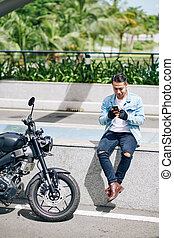 Smiling motorcyclist with smartphone