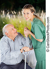 Smiling Nurse Helping Senior Man To Get Up From Couch