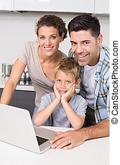 Smiling parents using laptop with their son