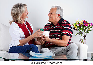 Smiling Senior Man Giving Gift to His Wife