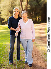 senior woman and caring daughter walking in forest