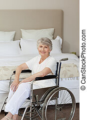 Smiling senior woman in her wheelchair