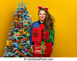 smiling stylish woman holding pile of Christmas present boxes
