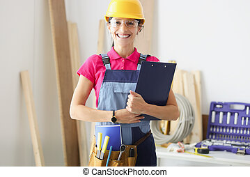 Smiling woman builder holds clipboard with documents in her hands