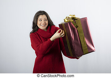 Smiling woman in a red sweater holding gift box with ribbon