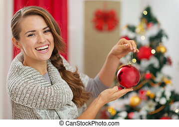 Smiling woman in front of Christmas tree holding Christmas ball