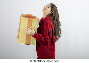 Smiling woman in red sweater holding Christmas present