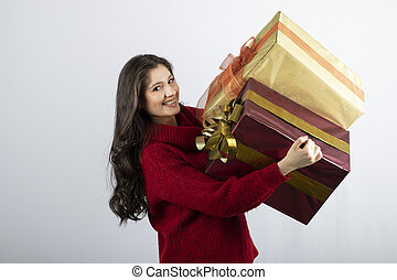 Smiling woman in red sweater holding Christmas presents