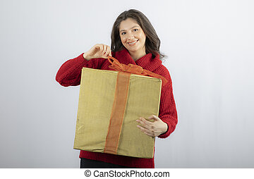 Smiling woman in red sweater opening a box of Christmas present