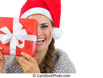 Smiling woman in Santa hat holding Christmas present