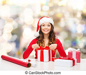 smiling woman in santa helper hat packing gifts