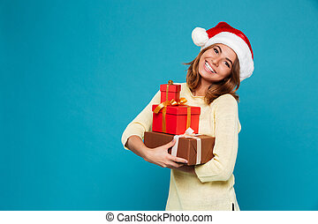 Smiling woman in sweater and christmas hat holding gift boxes