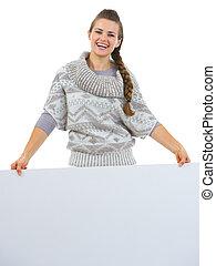 Smiling woman in sweater holding blank billboard