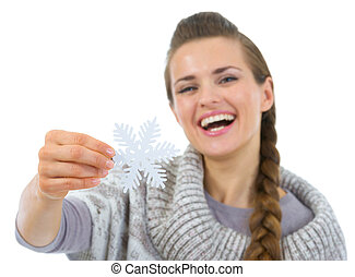 Smiling woman in sweater holding Christmas snowflake