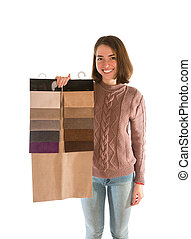 Smiling woman in sweater holding fabric swatches