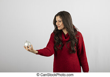 Smiling woman in warm red sweater offering a Christmas ball