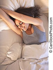 Smiling Woman on Bed Stretching Her Arms