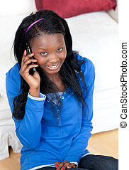 Smiling woman talking on phone in the living-room