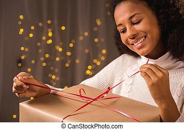 Smiling woman unwraping a present