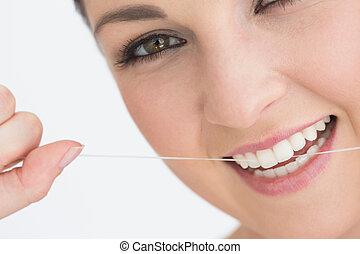Smiling woman using dental floss