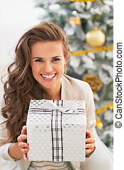 Smiling young woman holding christmas present box in front of christmas tree