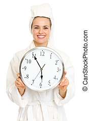 Smiling young woman in bathrobe holding clock