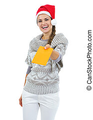 Smiling young woman in sweater and christmas hat giving letter