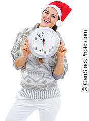 Smiling young woman in sweater and christmas hat showing clock