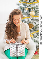 Smiling young woman opening christmas present box in front of christmas tree