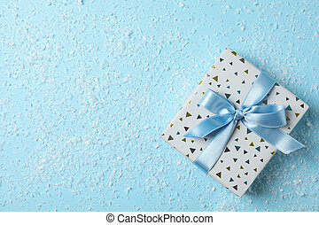 Snow and present with bow on blue background, space for text