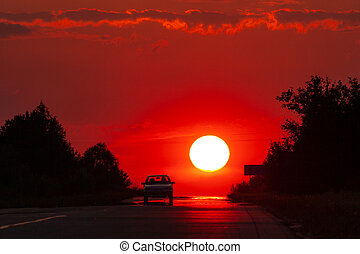 Solar disk and silhouettes of car against the background of the red sunset sky